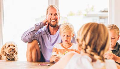 Happy man at home with his family - he is getting a great deal on power!