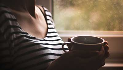 Woman enjoying a warm coffee inside a home sealed of air leaks and cold draughts