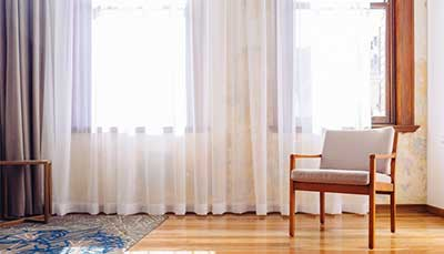 Warm curtains sitting open during the day to allow natural sun to warm the room